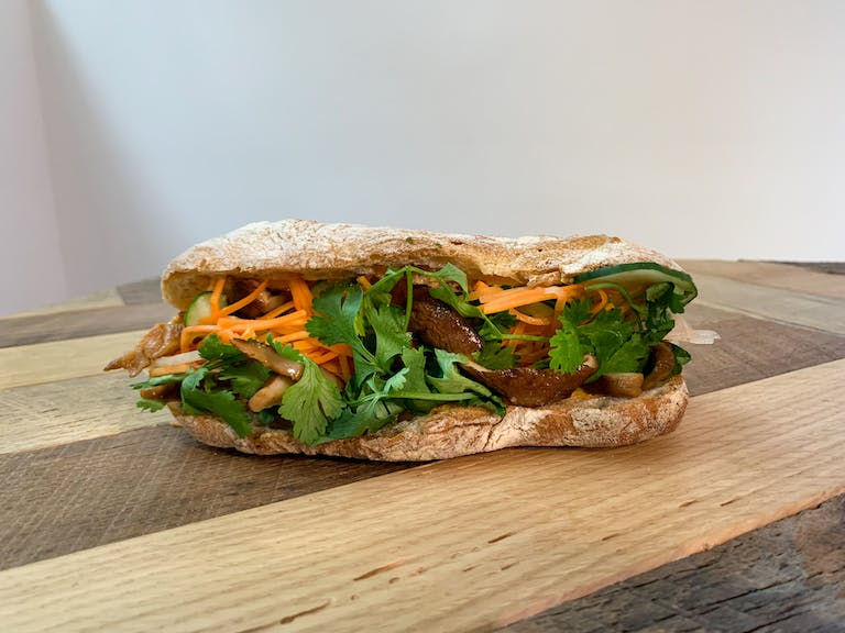 a Grilled Shiitake Banh Mi sandwich sitting on top of a wooden cutting board
