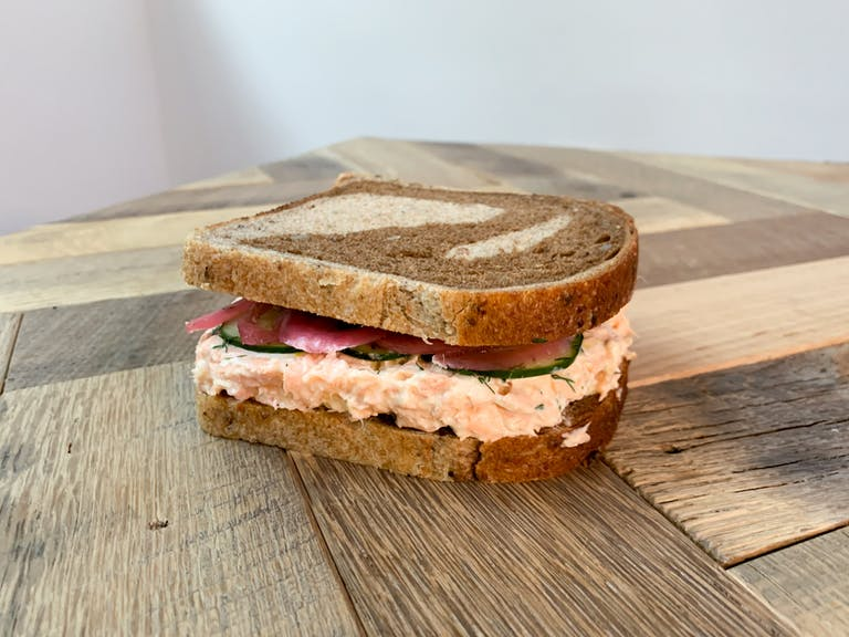 a Salmon Rillettes sandwich sitting on top of a wooden cutting board