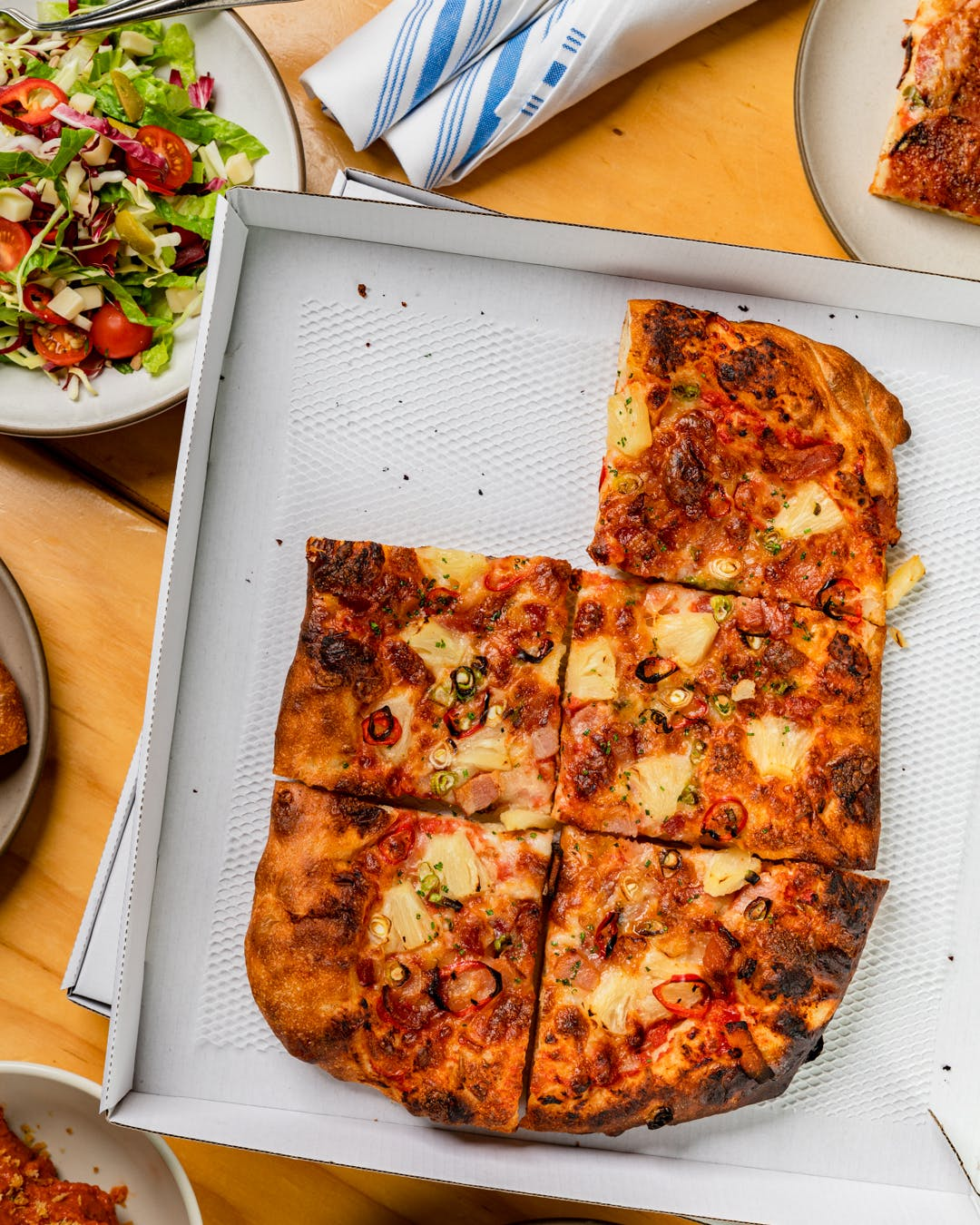 a plate of food with a slice of pizza in a box