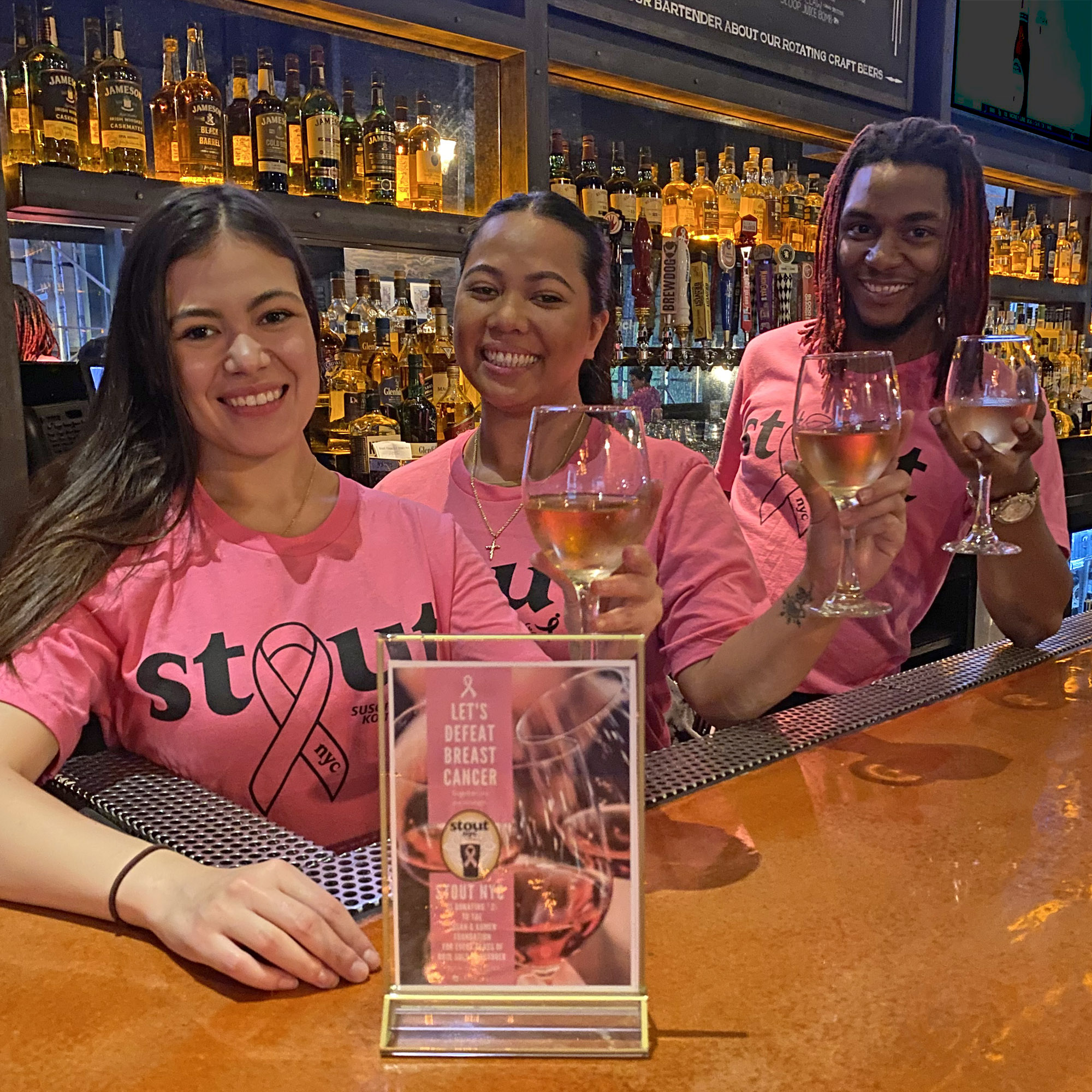 3 people in a bar wearing pink Stout NYC shirts holding glasses of rosé for Breast Cancer Awareness Month