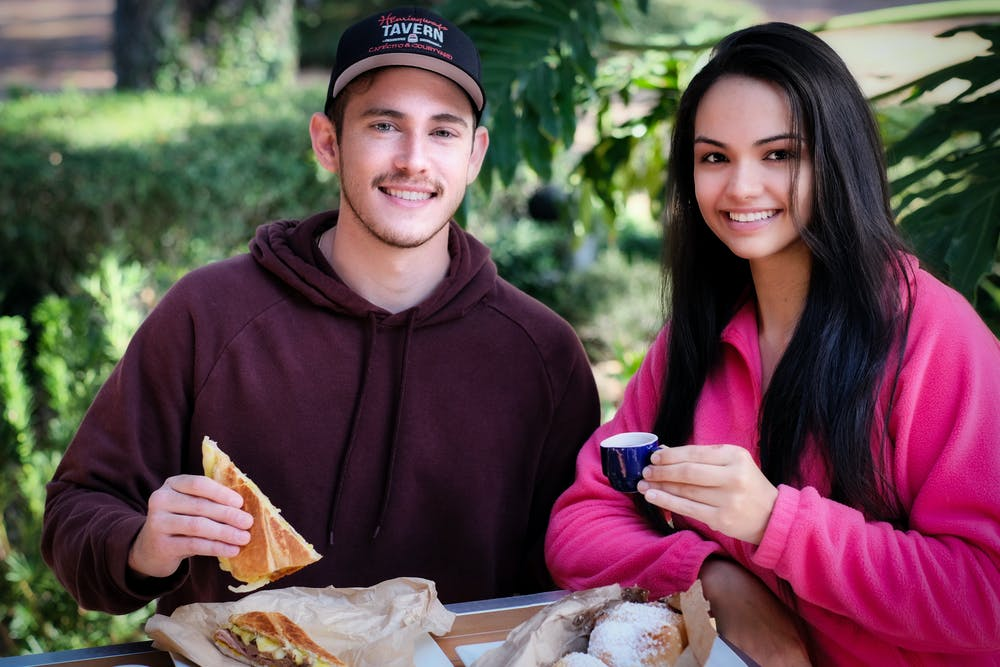 a man and a woman eating a sandwich