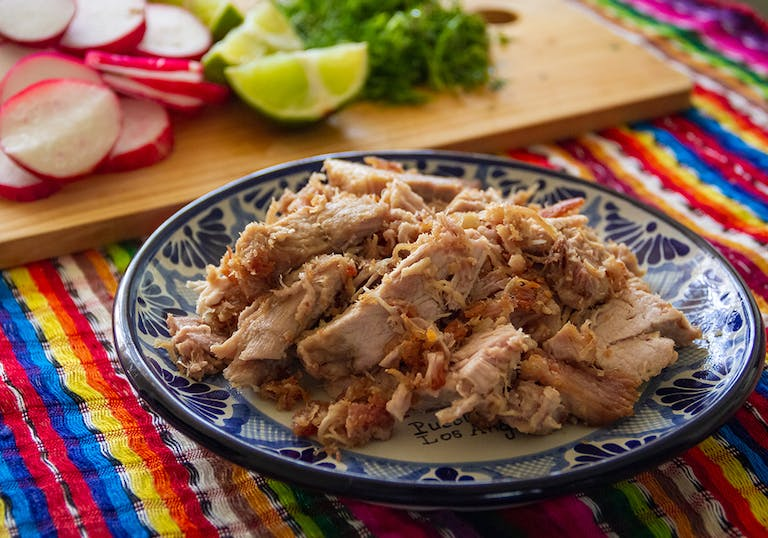 a plate of carnitas on a colorful tablecloth