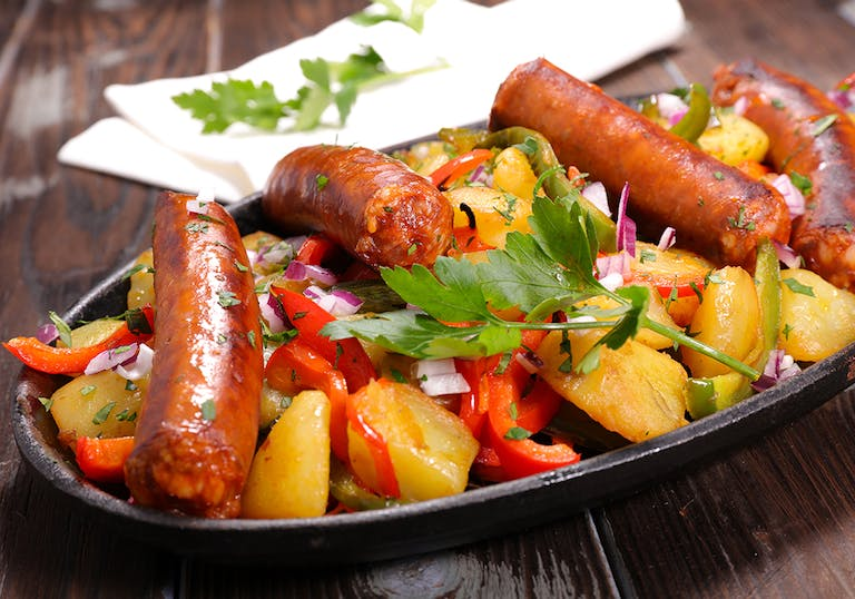 cooked italian sausage links and peppers on a plate