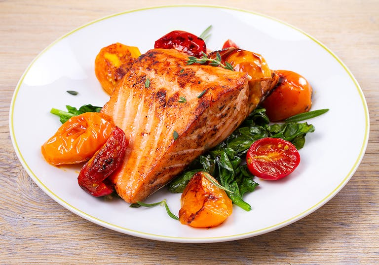 broiled salmon on a plate with garnish