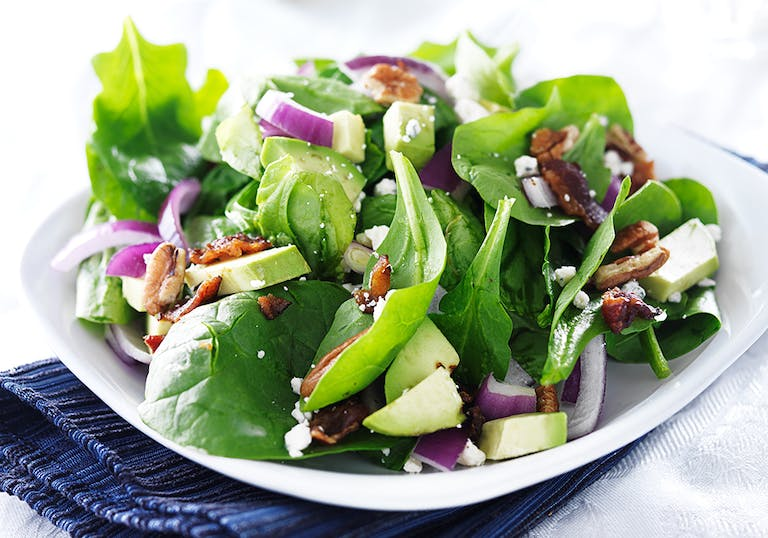 a salad with spinach and vegetables