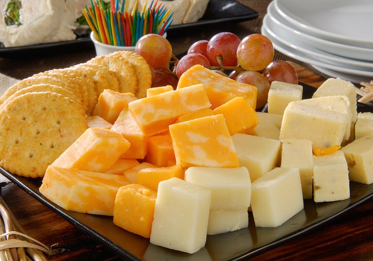 a variety of cubed cheeses with crackers