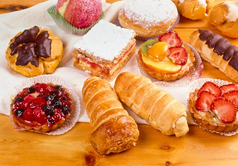 a variety of Italian pastries arranged on a wooden table