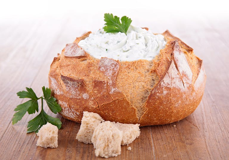 a bowl of sourdough bread filled with spinach dip