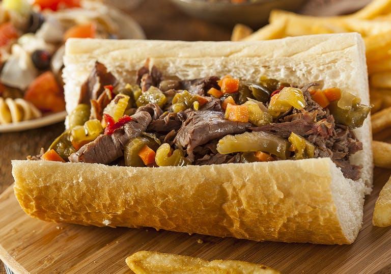 an italian beef sandwich on a wooden cutting board