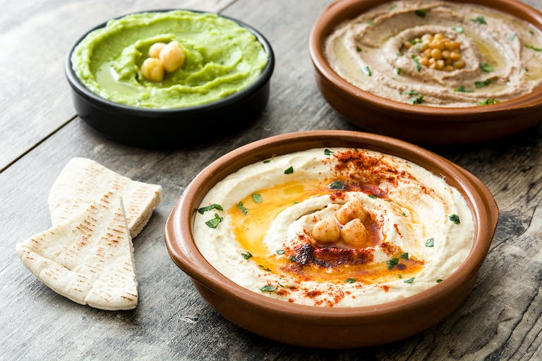 a variety of hummus in bowls with pita
