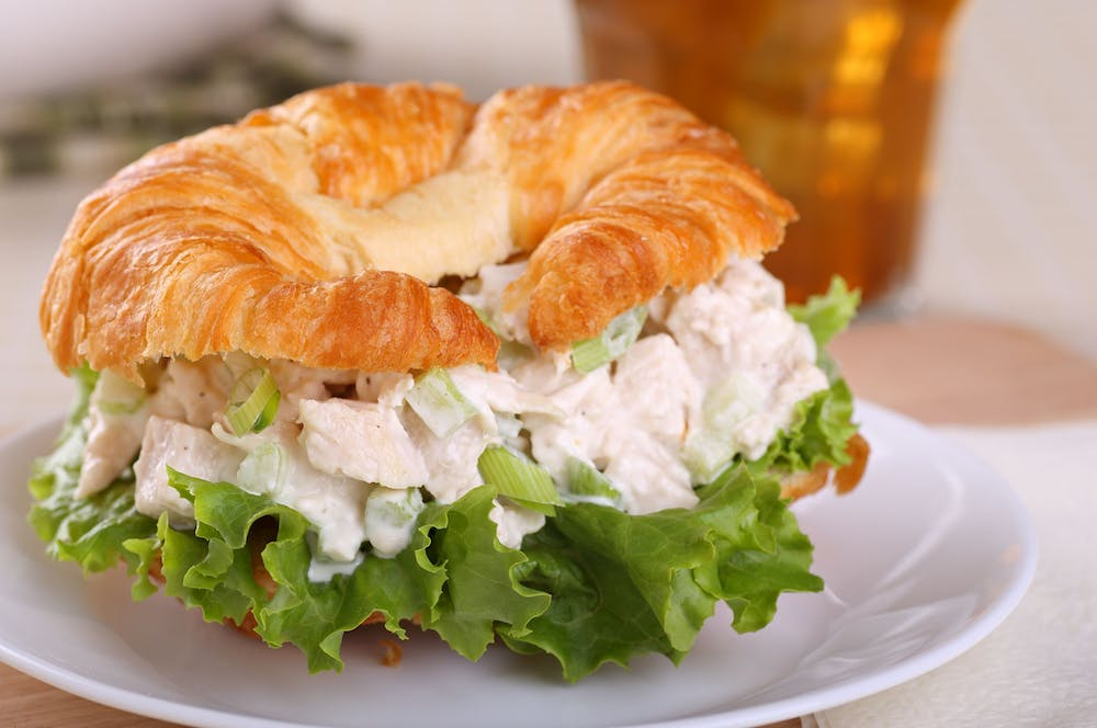 a close up of a white plate topped with a sandwich and a salad