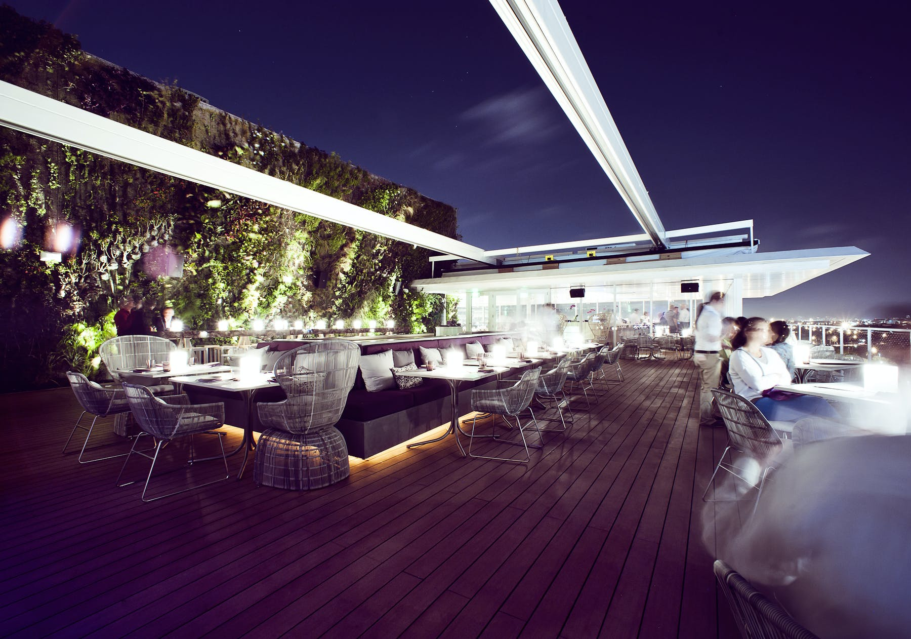 an extensive patio at night filled with lighten up tables and chairs