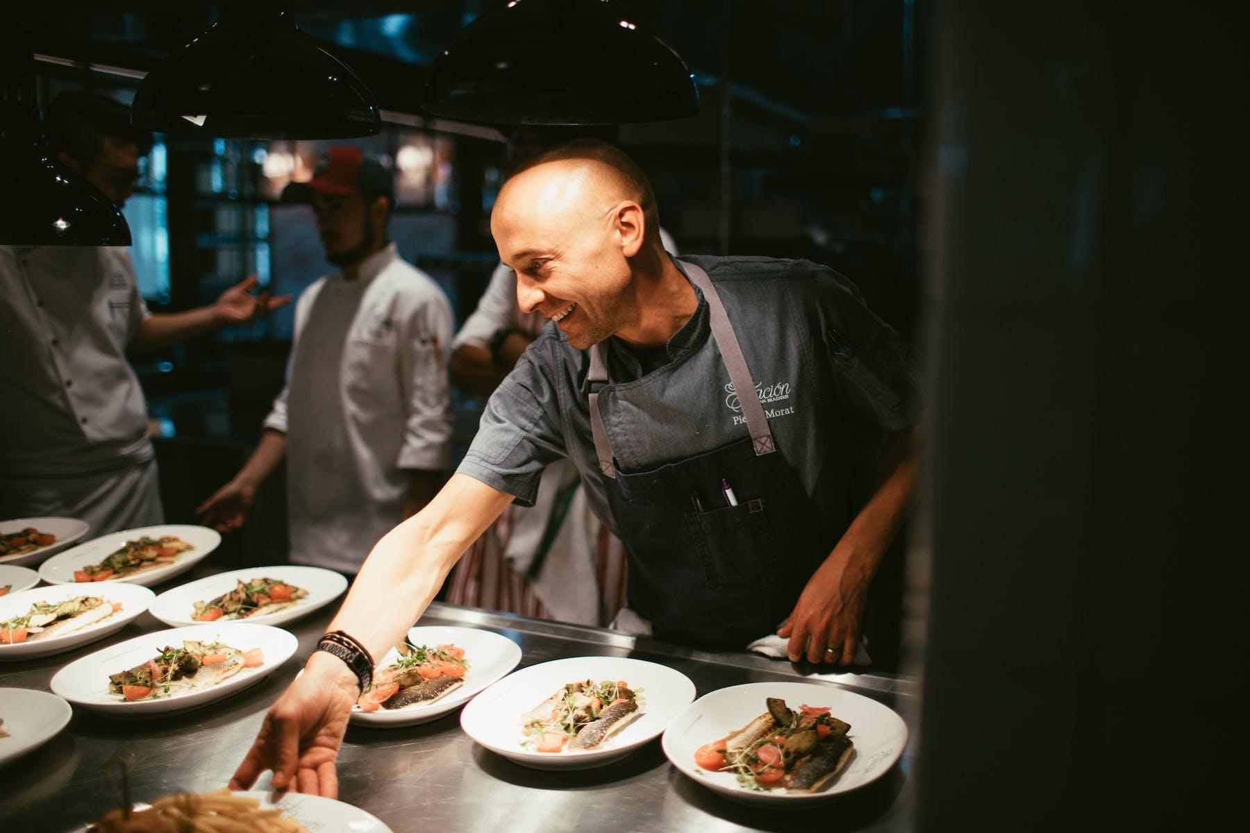 a man serving food on an open kitchen bar