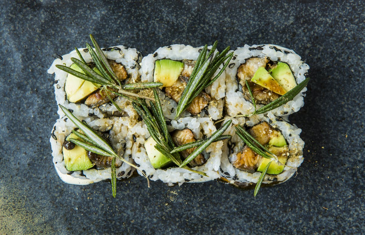 a close up of sushi rolls with avocado