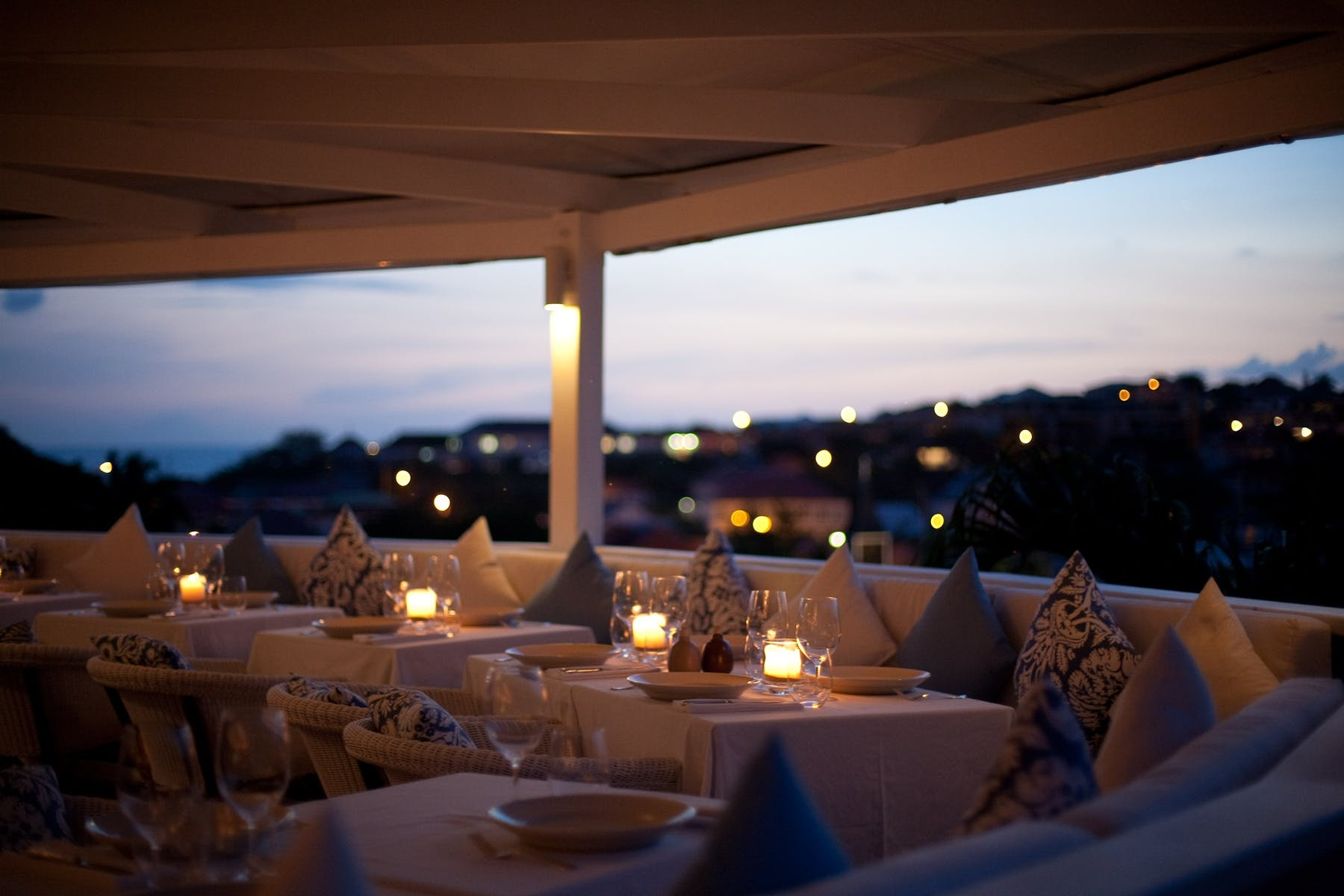 a terrace at night filled with tables and chairs
