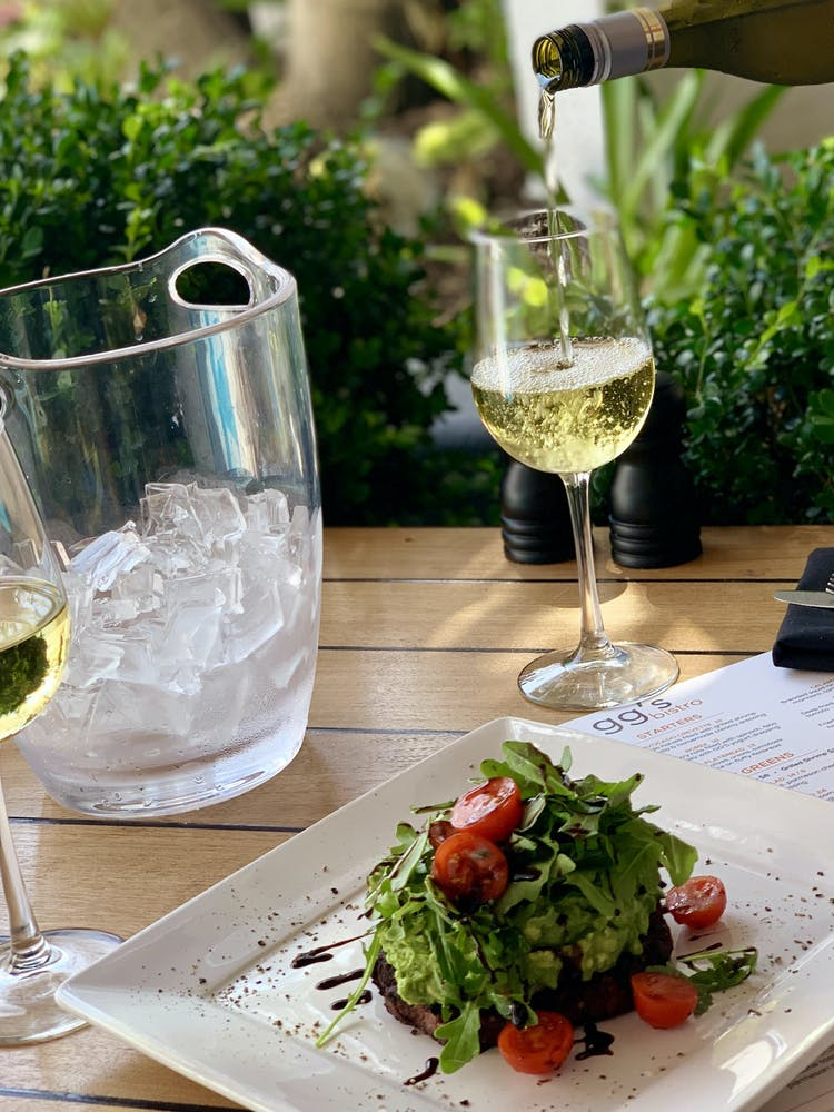 a close up of a plate of salad and a glass of wine