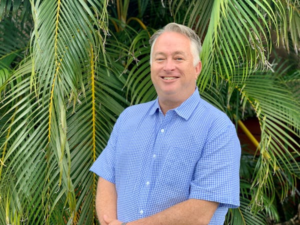 a man standing in front of a palm tree
