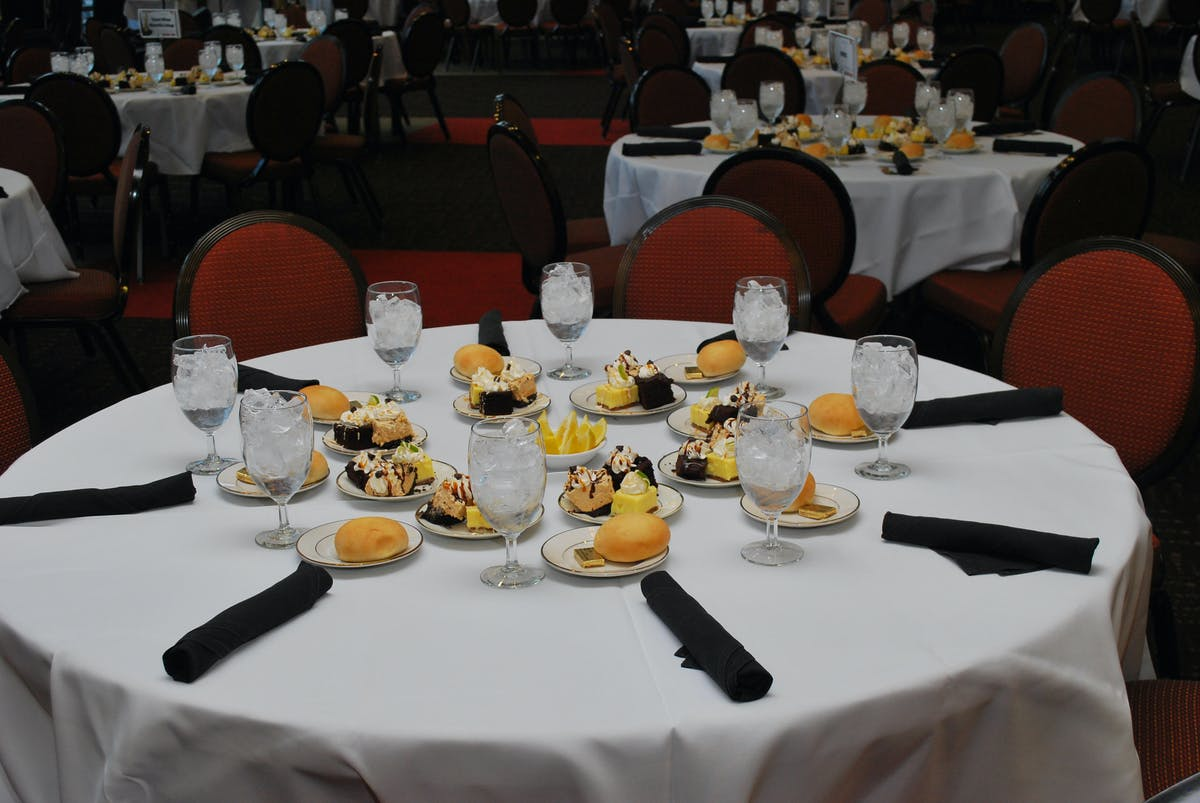 a round table with a white table cloth with desserts and bread plates with a glasses filled with ice