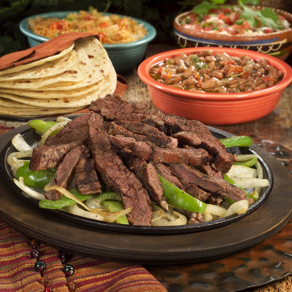 a set of plates topped with different types of foods, including vegetables, rice and carne asada