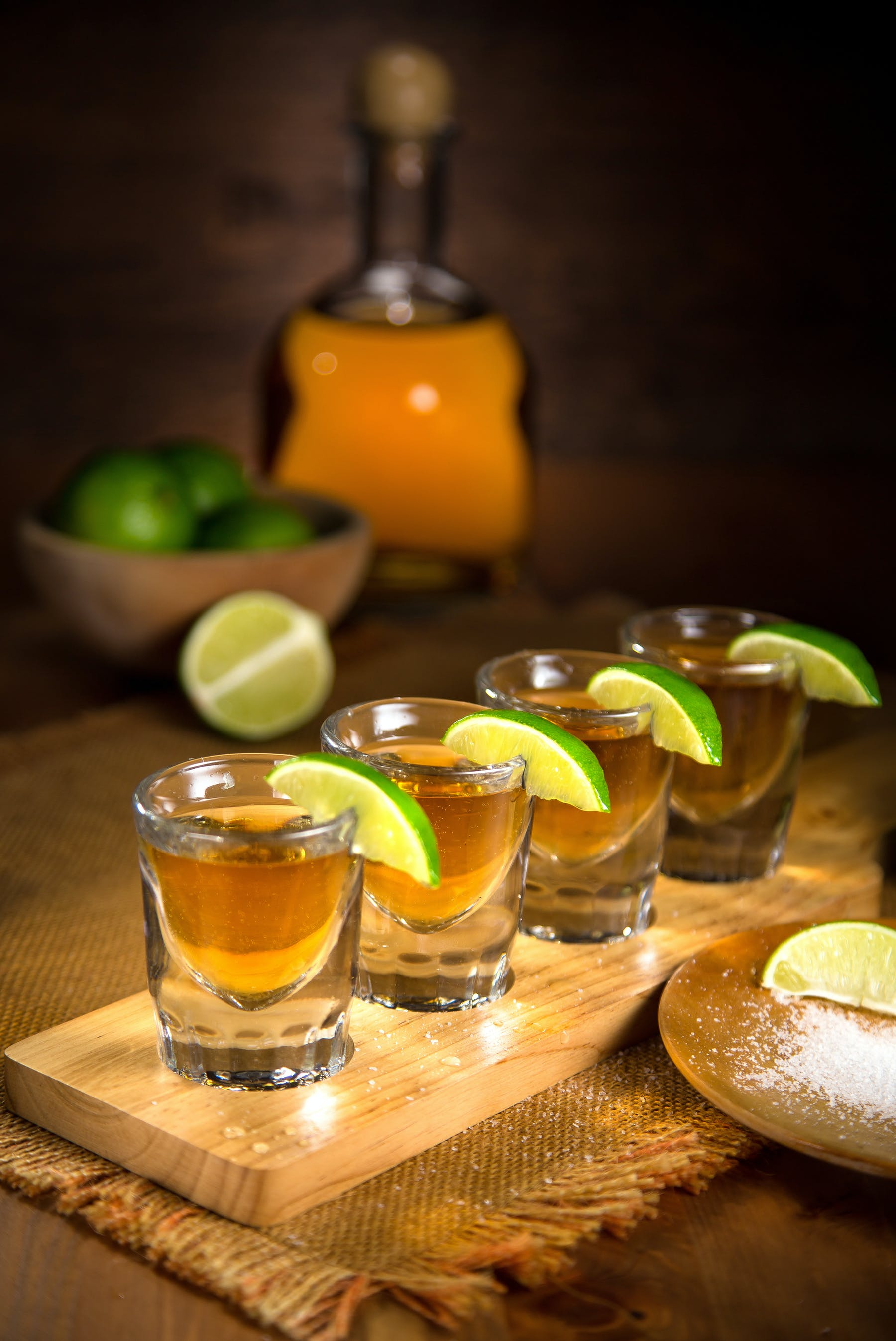 shots of tequila lined up sitting on a wooden cutting board