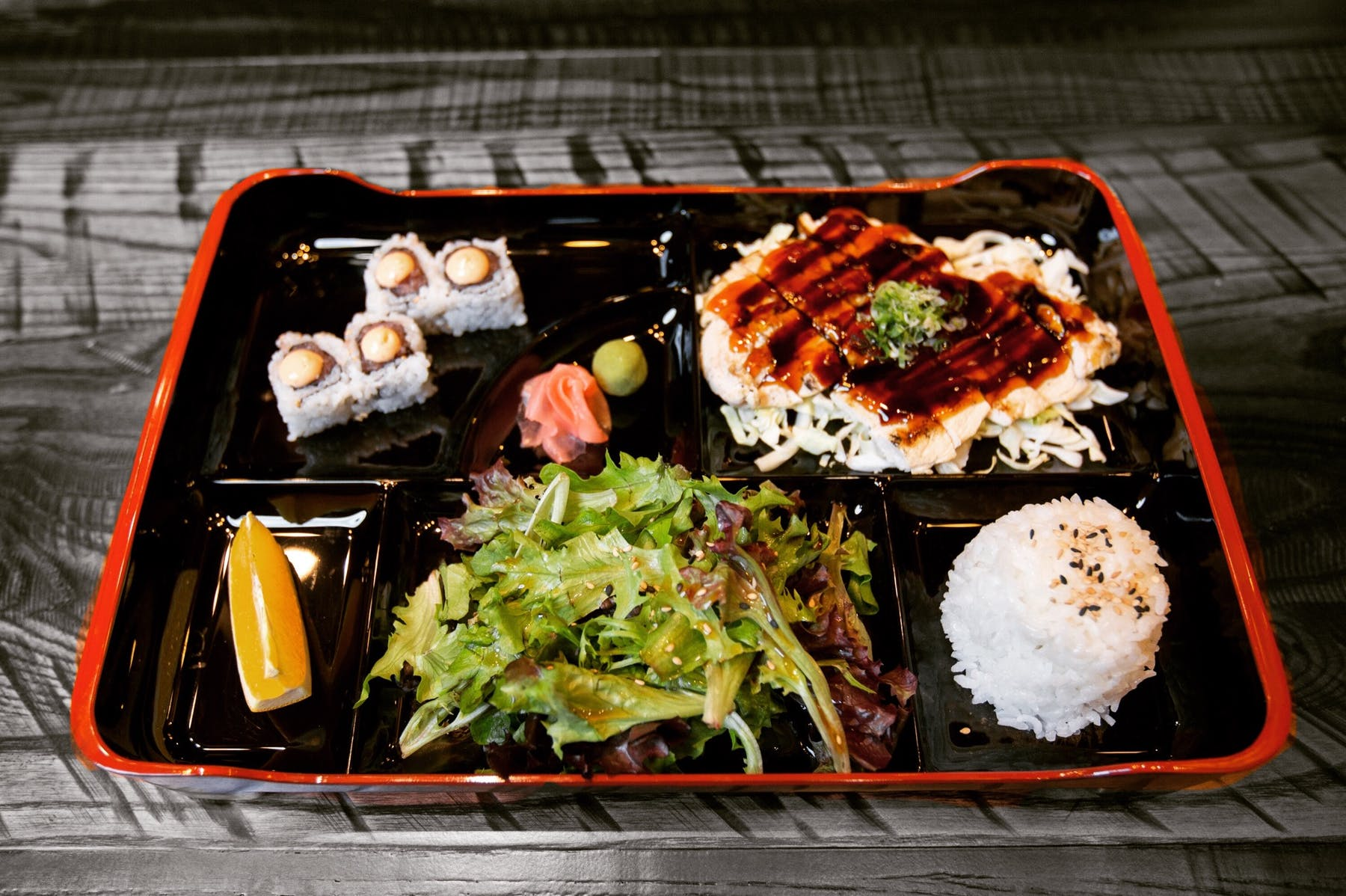 bentobox with different Japanese food, sushi rolls, white rice, coleslaw