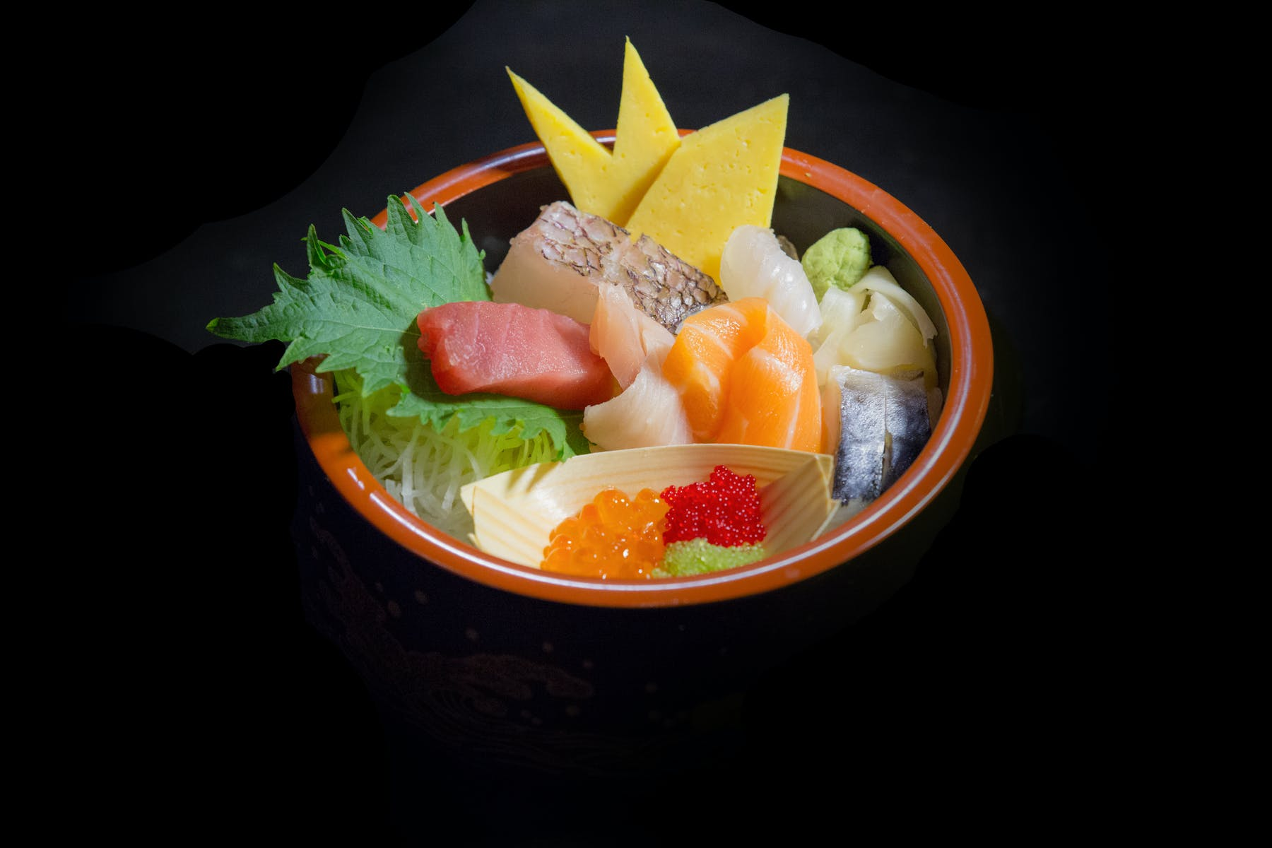 a bowl of fruit and sushi on a plate