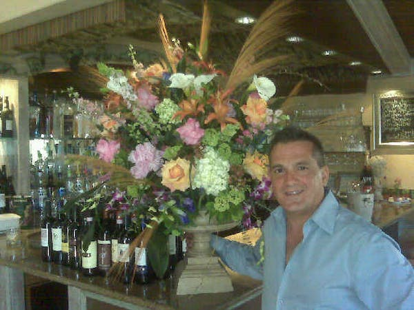 a person standing next to a vase of flowers on a table