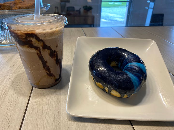 a chocolate doughnut and a cup of coffee on a table