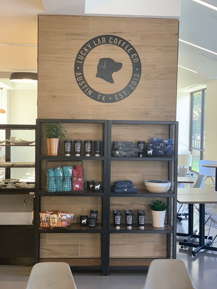 shelves with coffee tumblers and bags of coffee at the top is a circular logo with the drawing of a dogs face silhouette and on the border the address