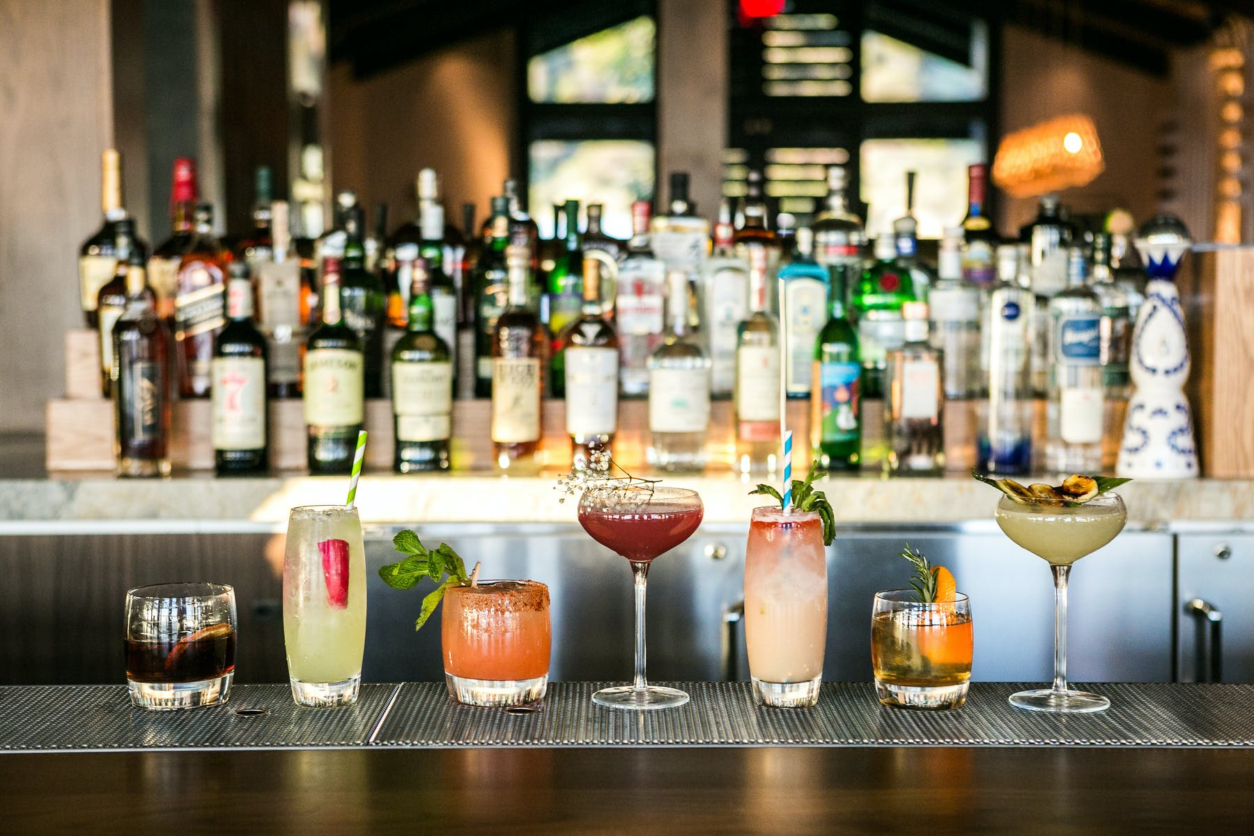 a line up of cocktails at the bar