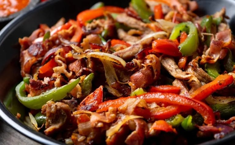 a dish is filled with meat and vegetables