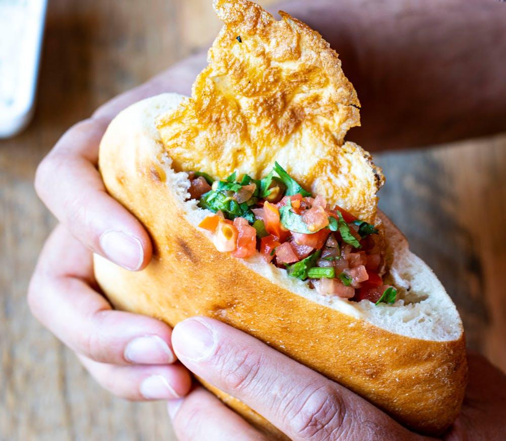 a hand holding a half eaten sandwich
