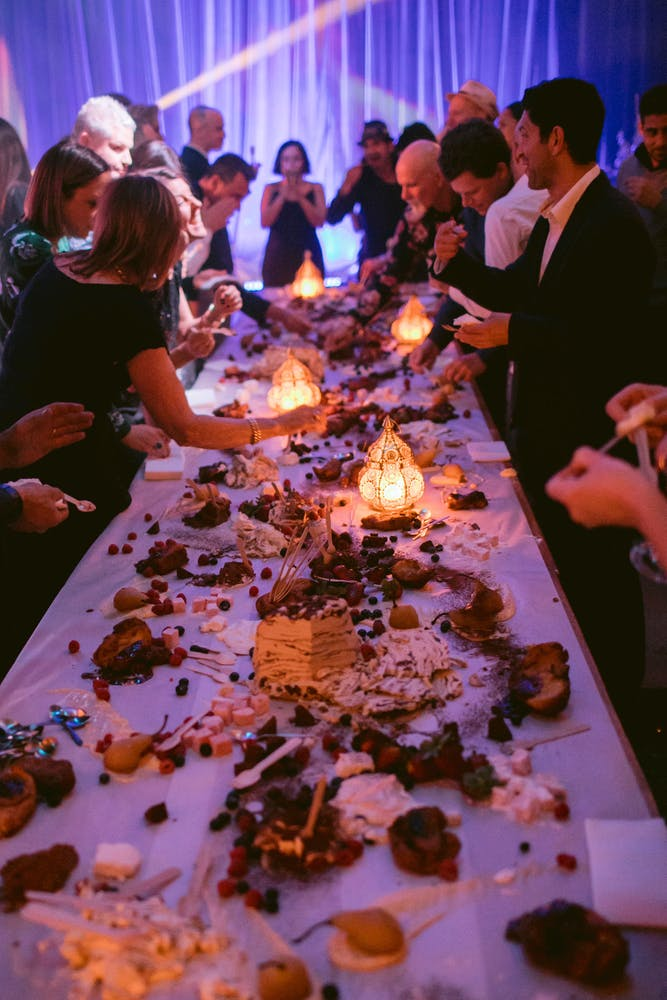 a group of people sitting at a table with a birthday cake