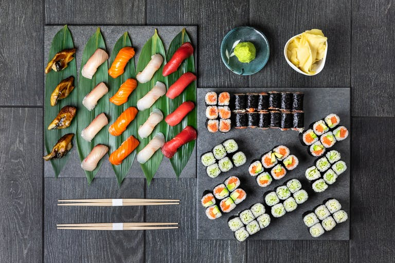 a group of sushi on a wooden surface