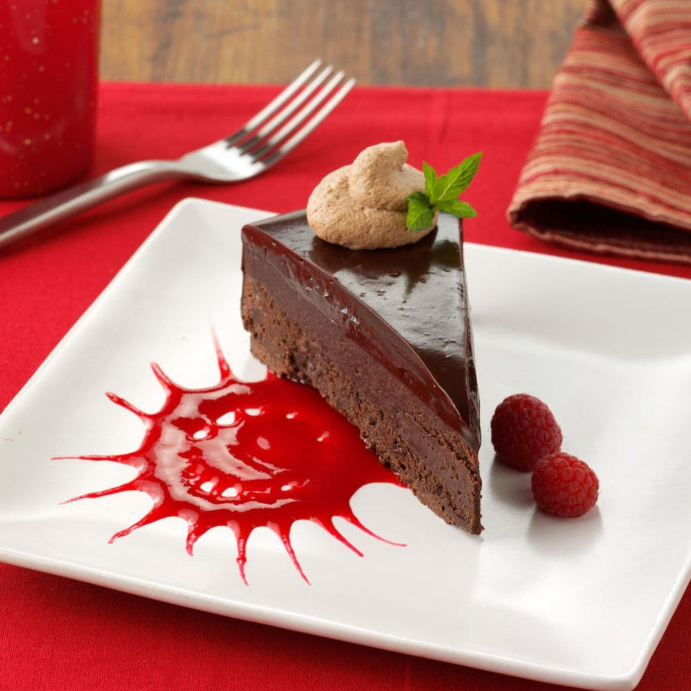 a piece of cake sitting on top of a red plate on a table