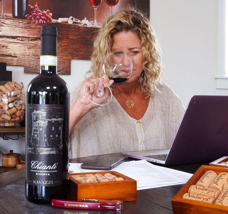 a person holding a bottle of wine on a table