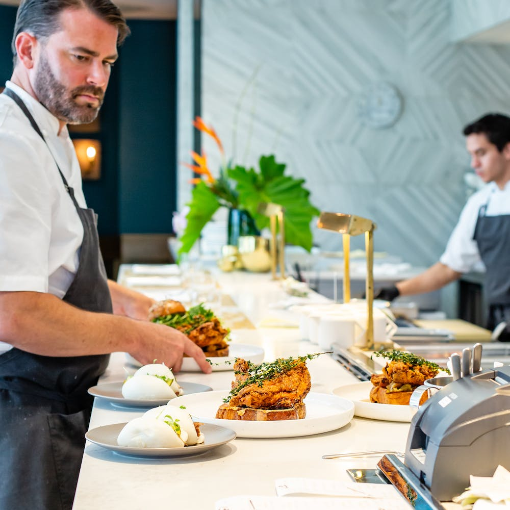 a close up of Chef Brian Vaughn plating food on a counter
