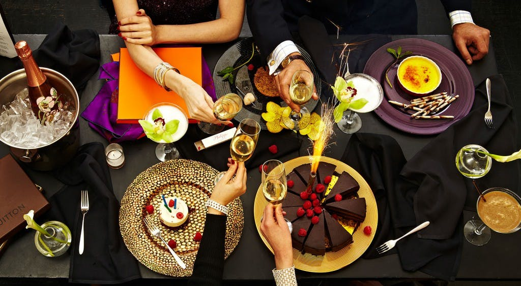a group of people sitting at a table with plates of food