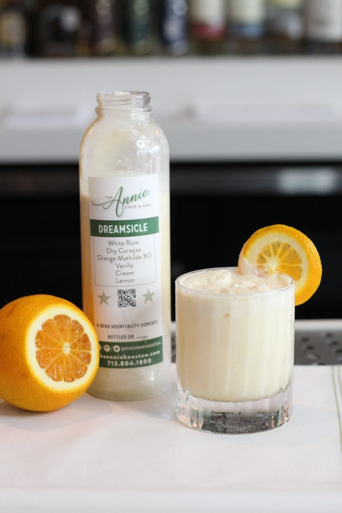 a close up of a bottle and a glass of orange juice