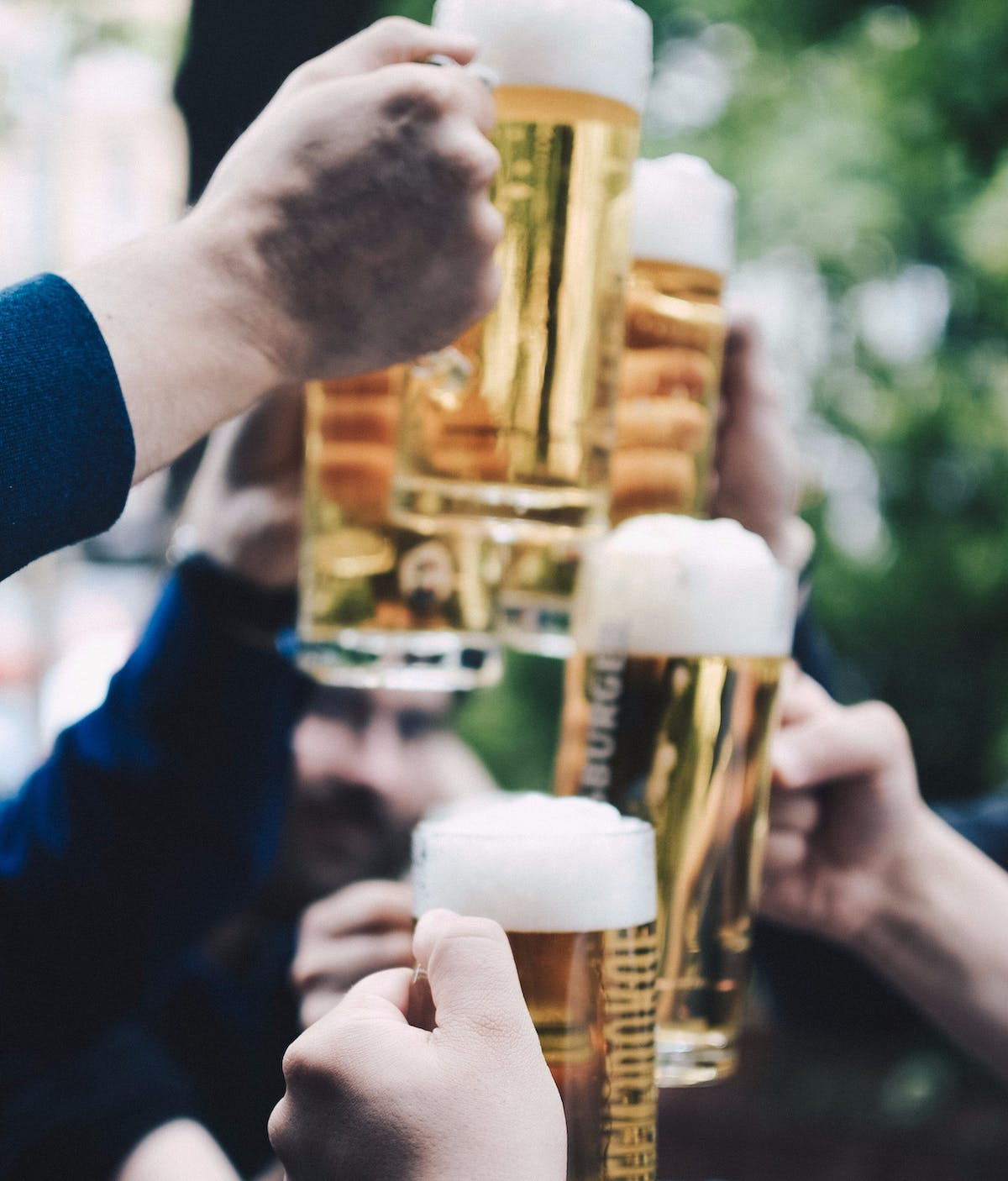 several people clinking beer glasses