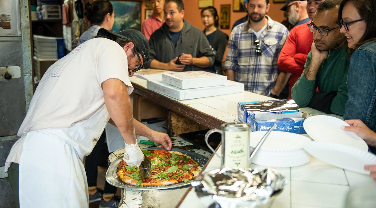 A group of people watching a pizza being prepared