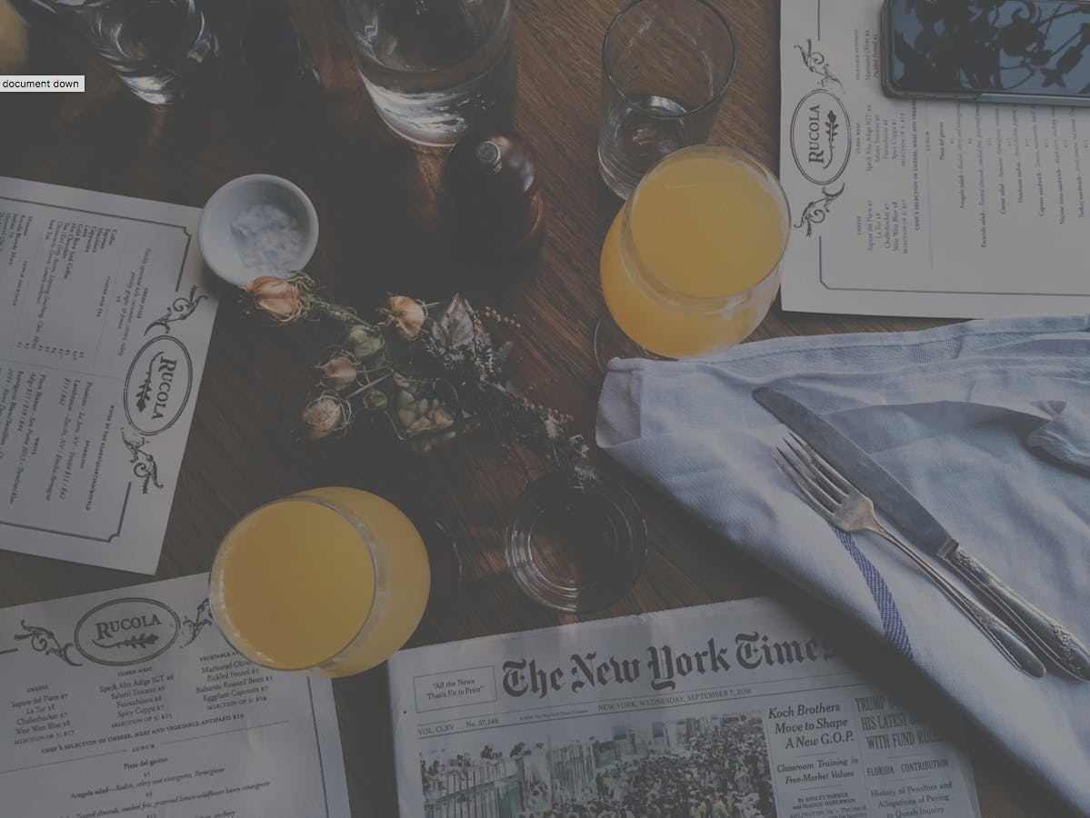 Restaurant menus, drinks and a newspaper on a table.