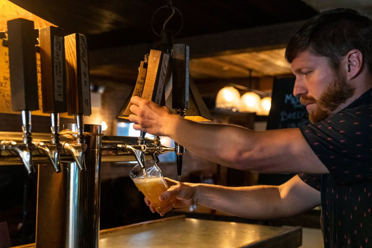 A man pouring a beer from the tap at a bar.