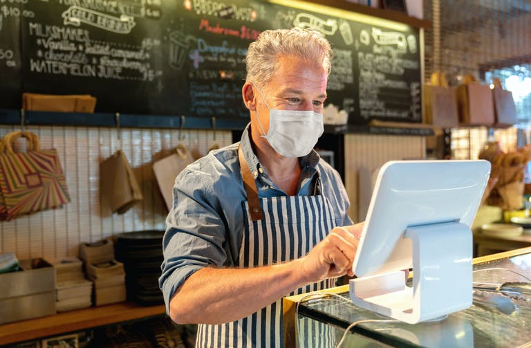 A restaurant owner using a tablet while wearing a mask