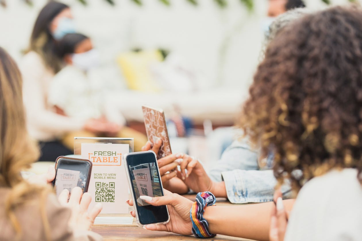 A group of diners using qr codes to view menus