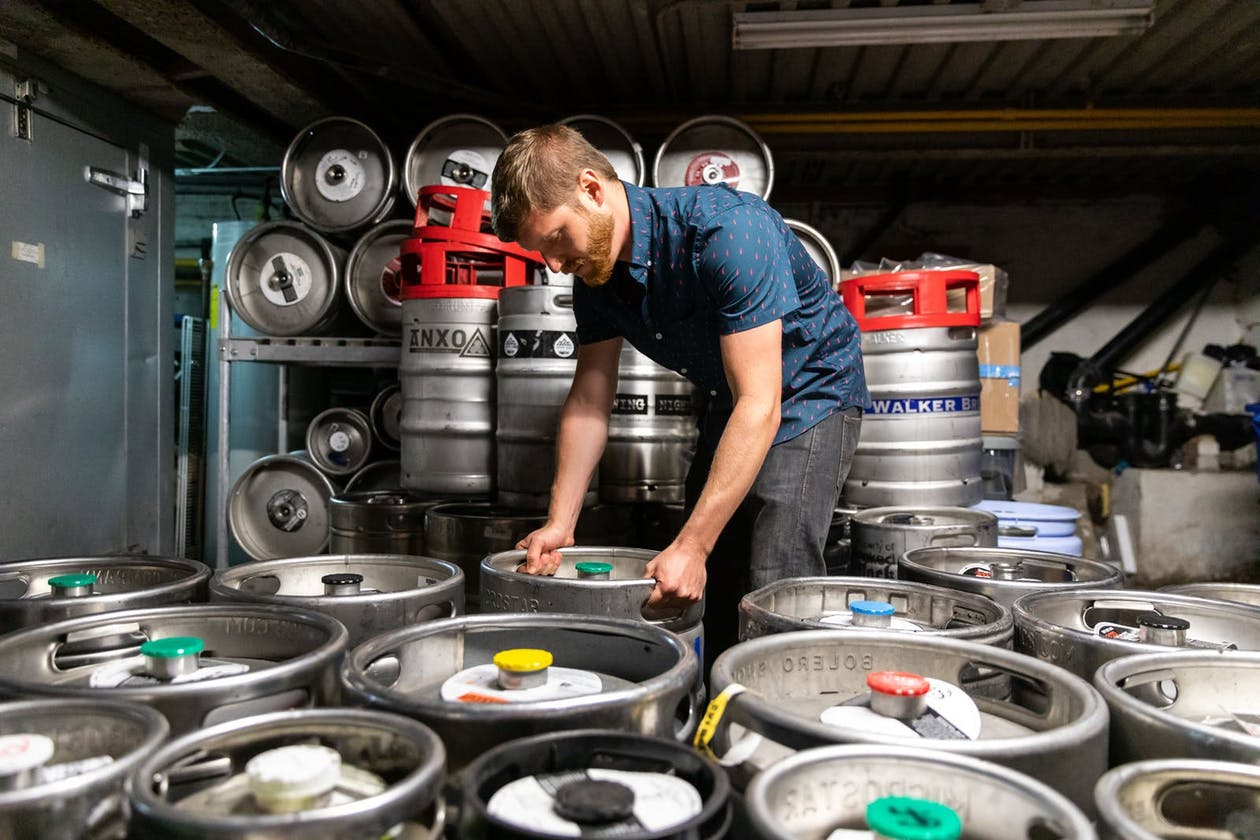 A man organizing kegs of beer in a basement.