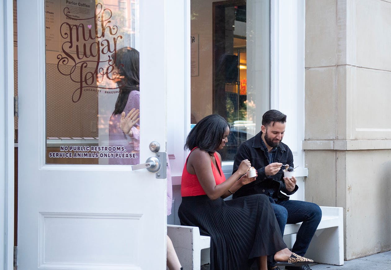 Two people eating ice cream on a bench