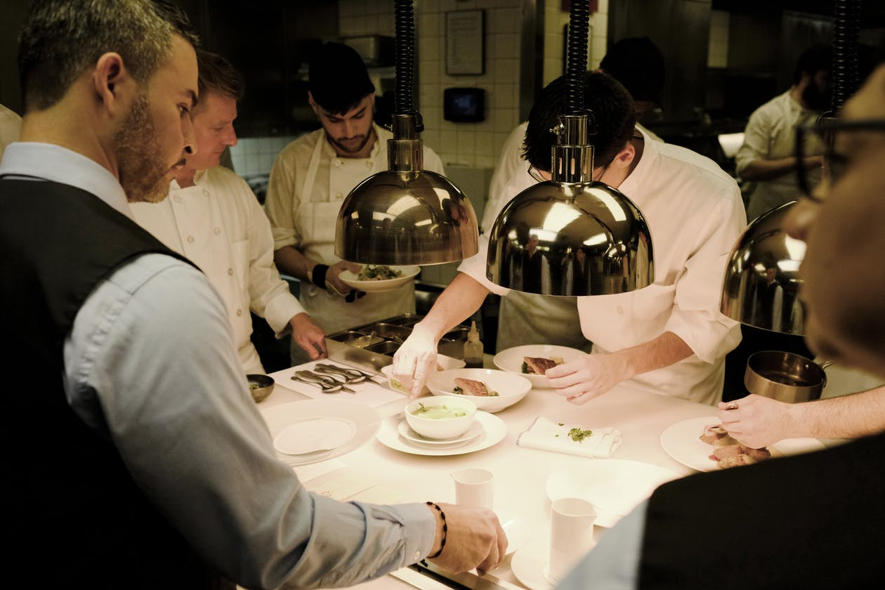 a group of people standing at a table prepping plates for service