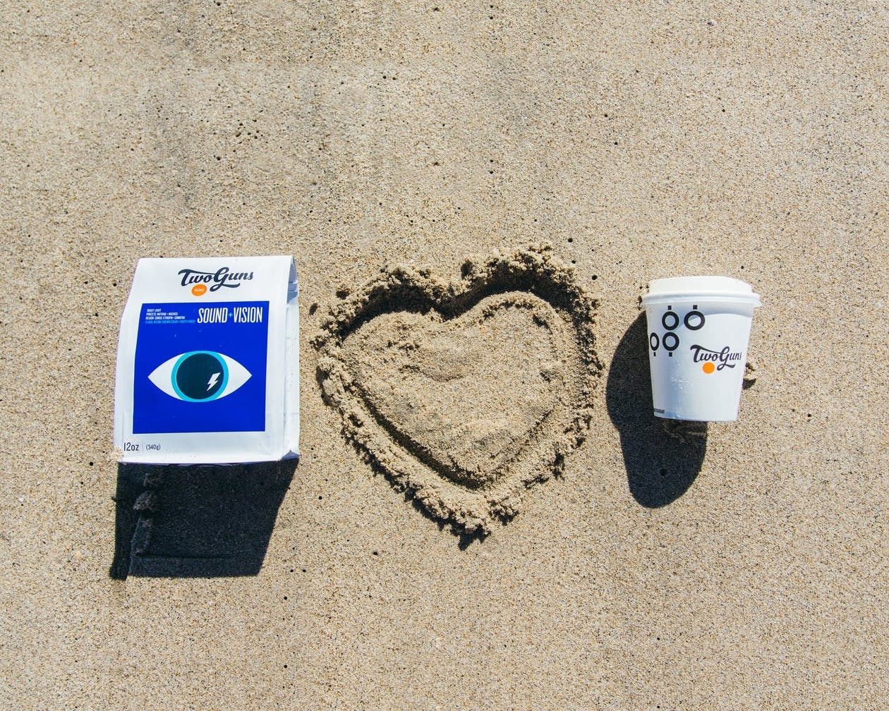 a coffee cup and bag of coffee on a sandy beach