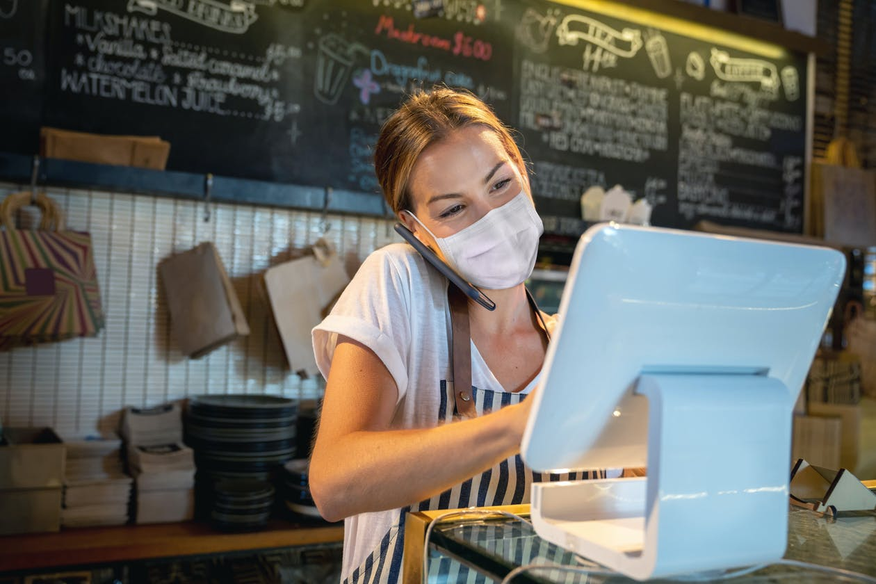A restaurant owner on the phone and using a POS